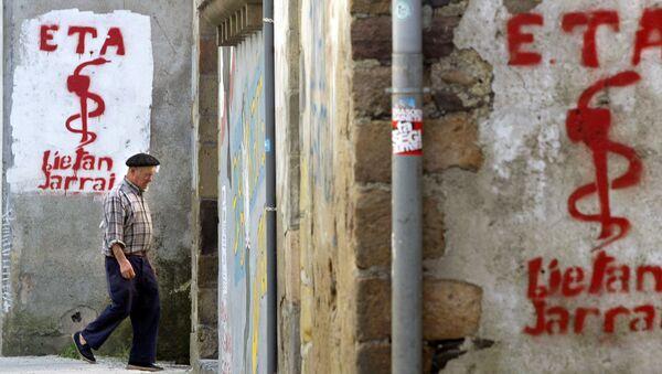 An old man walks past graffiti depicting the logo of Basque separatist group ETA in Goizueta - Sputnik Mundo
