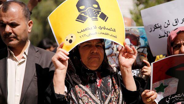 Una manifestante contraria al ataque aéreo de EEUU en Siria porta una pancarta en la que puede leerse: ¿Los productos químicos no afectan a los Cascos Blancos? - Sputnik Mundo