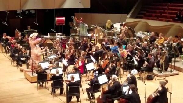 Cristopher Dragon, disfrazado de dinosaurio, dirige a su orquesta - Sputnik Mundo