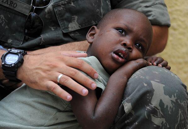 Un soldado de la Misión de las Naciones Unidas para la Estabilización en Haití (Minustah) abraza a un niño que quedó huérfano al morir sus padres en el terremoto de 2010. - Sputnik Mundo