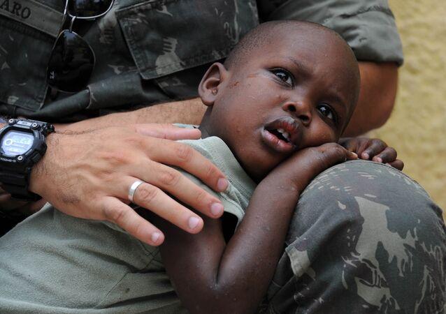 Un niño de Haití, en el regazo de un Casco Azul
