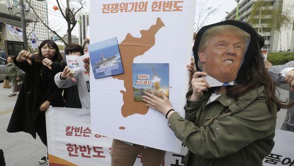 Los manifestantes llevan un recorte del presidente estadounidense Donald Trump y las imágenes del portaviones USS Carl Vinson y del sistema de defensa antimisiles estadounidense THAAD en un mapa de la Península Coreana - Sputnik Mundo