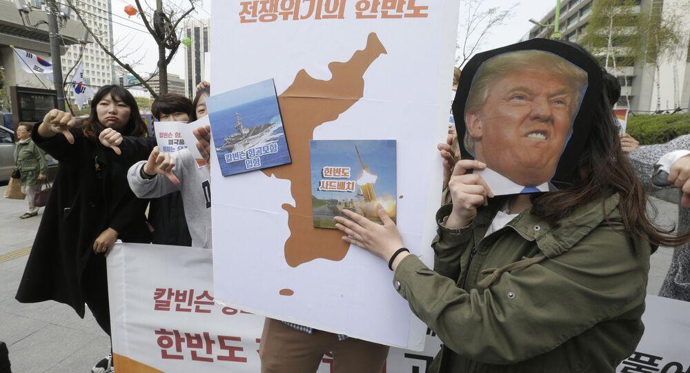 Los manifestantes llevan un recorte del presidente estadounidense Donald Trump y las imágenes del portaviones USS Carl Vinson y del sistema de defensa antimisiles estadounidense THAAD en un mapa de la Península Coreana