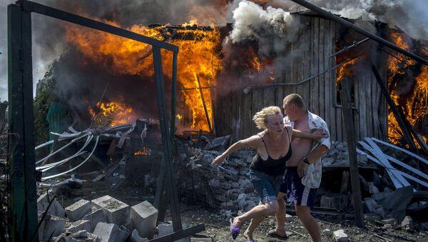 Lugareños de Stanitsa Lugánskaya huyen del incendio producido por un ataque de la Fuerza Aérea de Ucrania, 2 de julio de 2014 - Sputnik Mundo