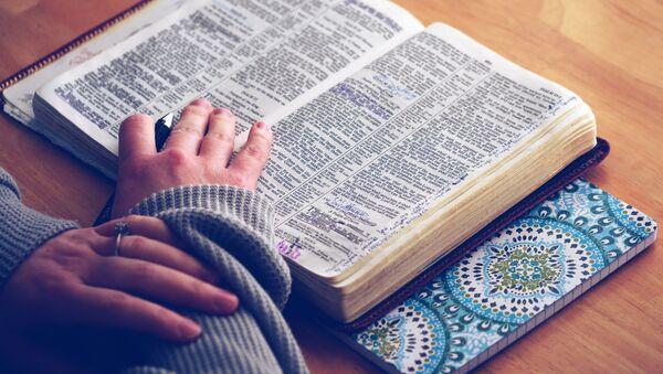 Una persona lee una biblia - Sputnik Mundo