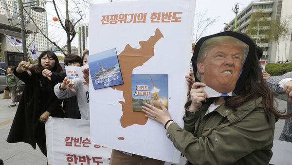 Protesters hold a cutout of U.S. President Donald Trump and images of the USS Carl Vinson aircraft carrier and U.S. missile defense system THAAD, right, on a map of Korean Peninsula during a rally against U.S. deployment of the aircraft carrier to the Korean Peninsula, near the U.S. embassy in Seoul, South Korea, Thursday, April 13, 2017 - Sputnik Mundo