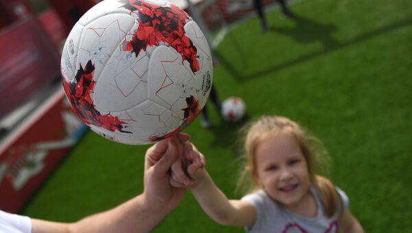 Una niña sostiene un balón en el primer parque temático de la Copa Confederaciones 2017 en Moscú - Sputnik Mundo