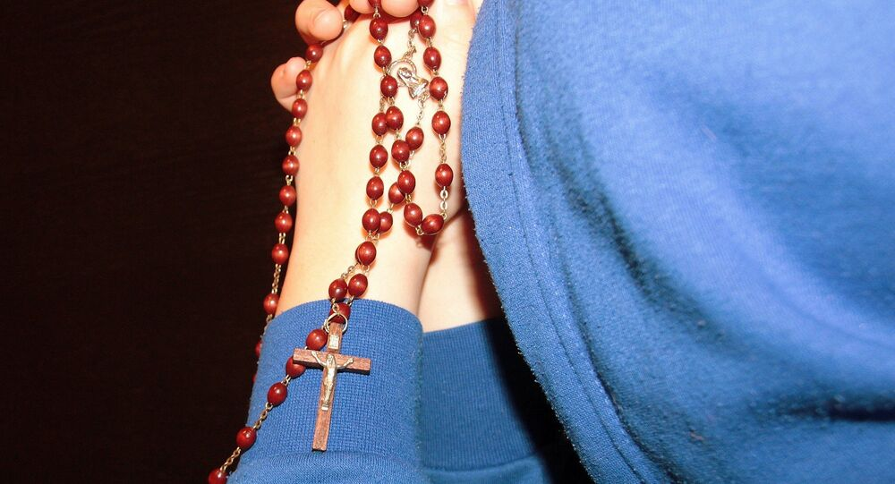 Un niño reza con un rosario