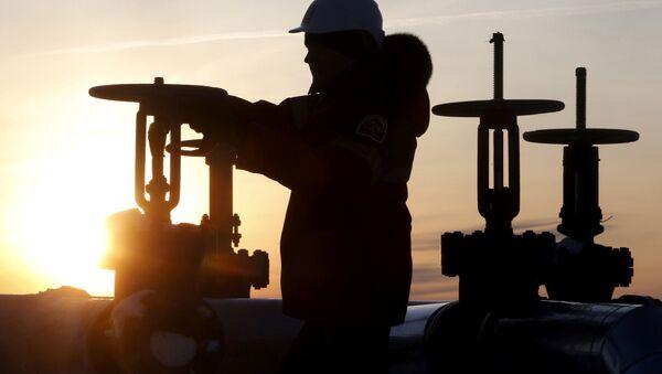Un obrero revisa la válvula de un tubo de petróleo - Sputnik Mundo