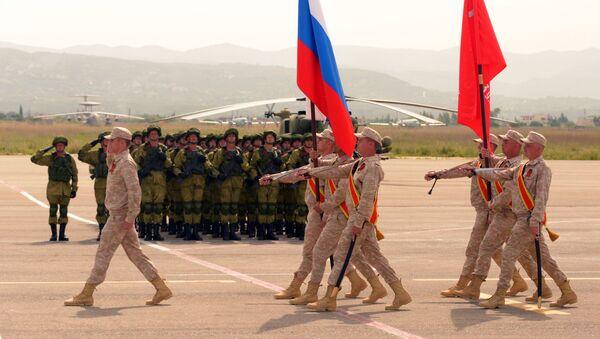 Los militares rusos durante el desfile militar del Día de la Victoria en la base aérea siria Hmeymim - Sputnik Mundo