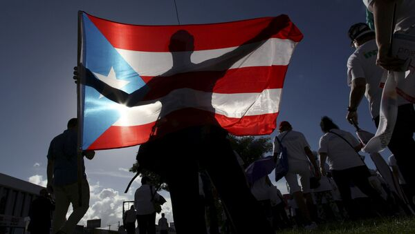 A protester holding a Puerto Rico's flag takes part in a march to improve healthcare benefits in San Juan - Sputnik Mundo
