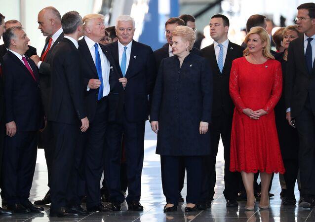 Donald Trump ajusta su chaqueta después de empujar al primer ministro de Montenegro Dusko Markovic