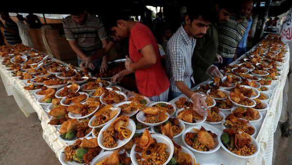 Unas personas organizan platos de comida para que los transeúntes interrumpan su ayuno durante un mes de Ramadán en Karachi - Sputnik Mundo