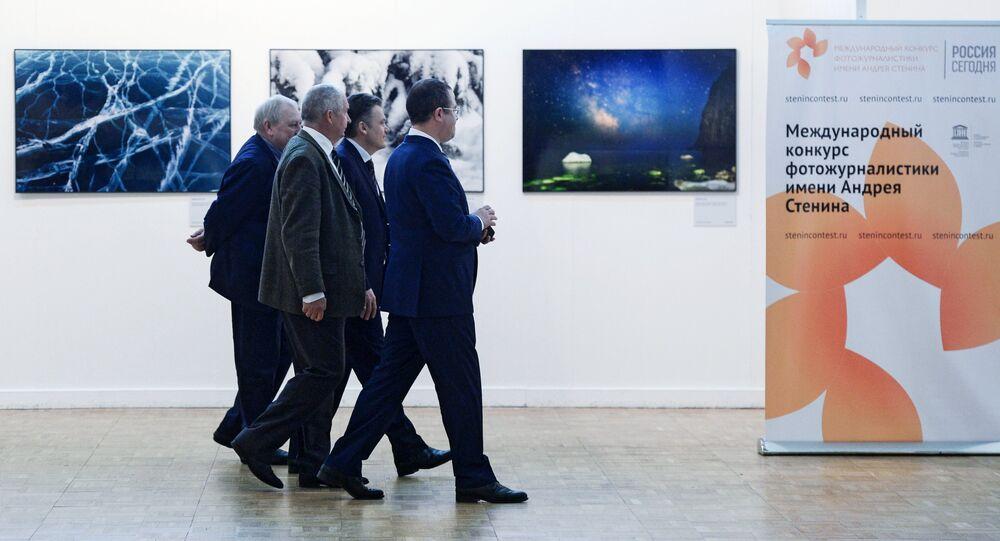 Los visitantes de la exhibición fotográfica pasan por el cartel del concurso de Andréi Stenin