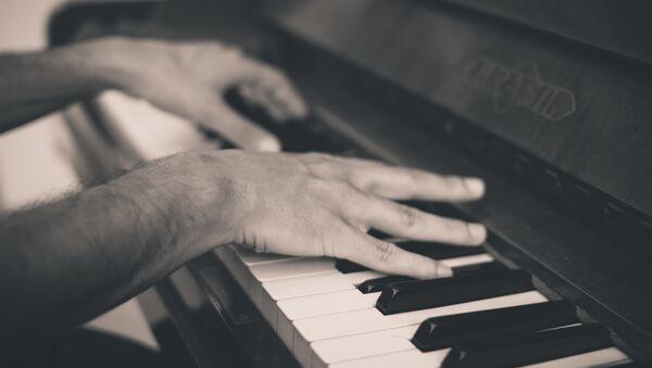 Un hombre tocando piano (imagen referencial) - Sputnik Mundo