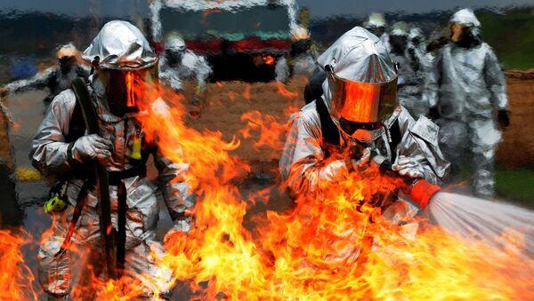 Unos bomberos intentan apagar el fuego (imagen referencial) - Sputnik Mundo