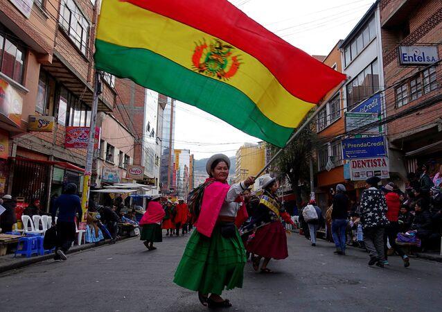 Una mujer indígena con la bandera de Bolivia