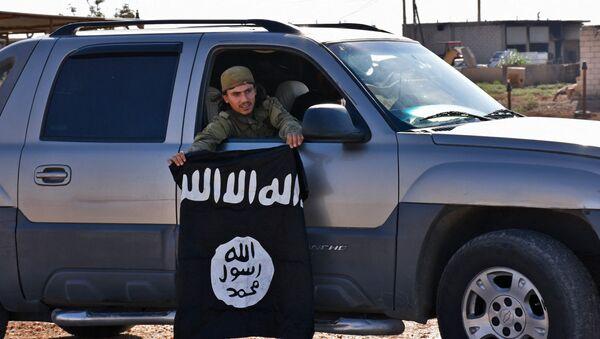 Un combatiente pro-gubernamental sirio demuestra la bandera de Daesh sacada de una aldea liberada - Sputnik Mundo