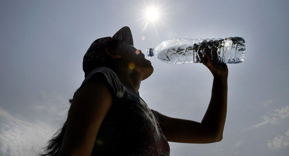 Una mujer bebe agua durante una ola de calor en Europa