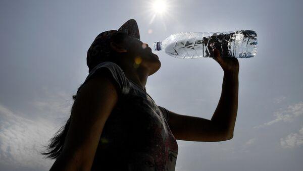 Una mujer bebe agua durante una ola de calor en Europa - Sputnik Mundo