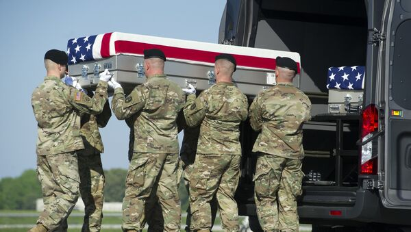 Un equipo de transporte del Ejército de EEUU coloca una caja que contiene los restos de su colega - Sputnik Mundo