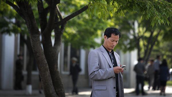 Un hombre con un teléfono celular - Sputnik Mundo