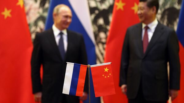 The Russian and Chinese national flags are seen on the table as Russia's President Vladimir Putin (back L) and his China's President Xi Jinping (back R) stand during a signing ceremony at the Diaoyutai State Guesthouse in Beijing on November 9, 2014. - Sputnik Mundo