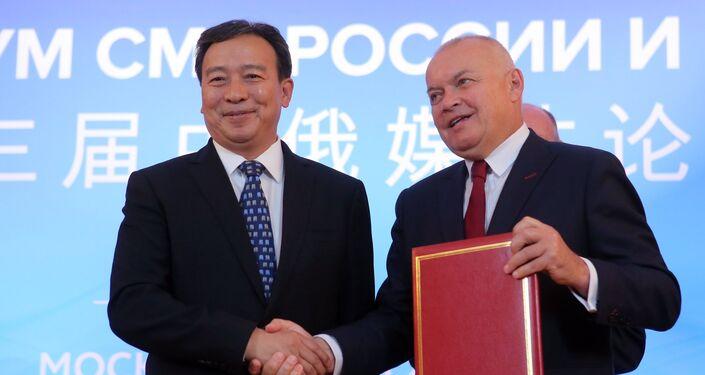 El vice redactor jefe de la compañía de radio y televisión de Guangdong, Shi Yanfeng, y el director general de la agencia Rossiya Segodnya, Dmitri Kiseliov