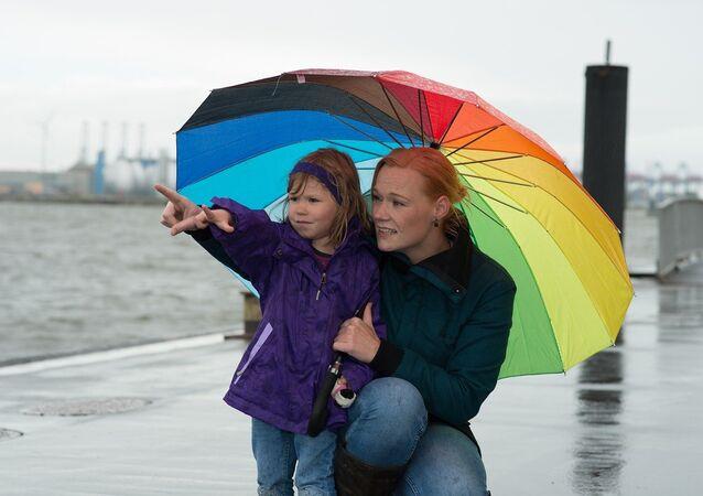 Una mujer con su hija bajo la lluvia