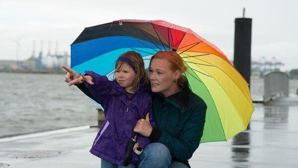 Una mujer con su hija bajo la lluvia - Sputnik Mundo