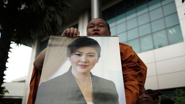 Un monje con la foto de la ex primera ministra de Tailandia, Yingluck Shinawatra - Sputnik Mundo