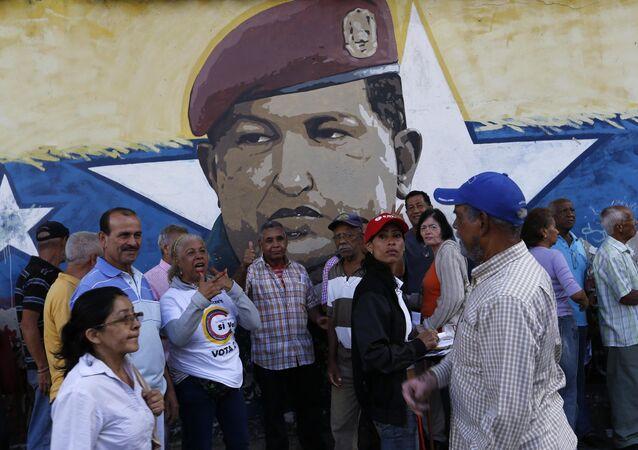 La gente venezolana ante una muralla con la imágen del expresidente de Venezuela, Hugo Chávez (archivo)