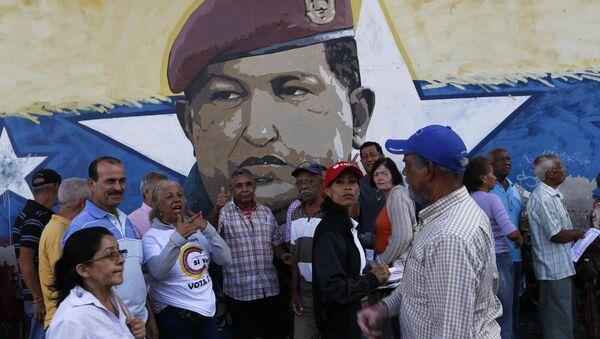 La gente venezolana ante una muralla con la imágen del expresidente de Venezuela, Hugo Chávez - Sputnik Mundo