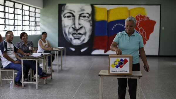 Electoral officials watch as a woman casts her vote at a polling station during the Constituent Assembly election in Caracas, Venezuela - Sputnik Mundo