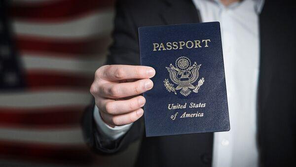 Un hombre sostiene un pasaporte estadounidense - Sputnik Mundo