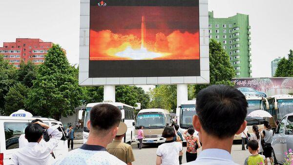 Personas observando el nuevo lanzamiento del misil en un estación de Pyongyang - Sputnik Mundo