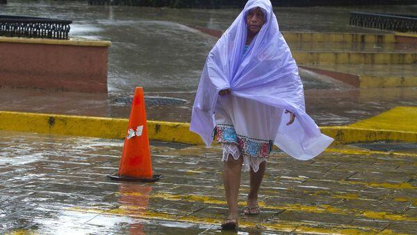 Una mujer se cubre de la lluvia tropical causada por el huracán Franklin - Sputnik Mundo