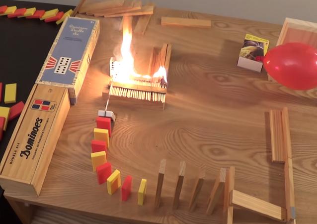 Una reacción en cadena incendiaria con dominós, velas y mucho fuego