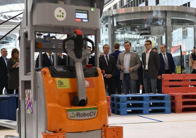 El fundador de RoboCV, Serguéi Máltsev (traje gris), presenta su robot-montacargas al primer ministro ruso, Dmitri Medvédev (a la izquierda de Máltsev)