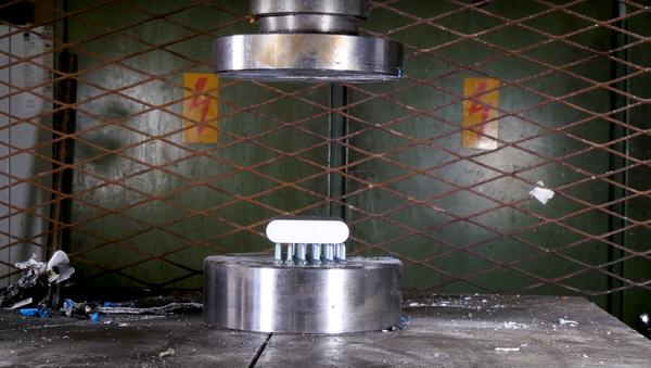 Batería colocada en una prensa hidráulica - Sputnik Mundo