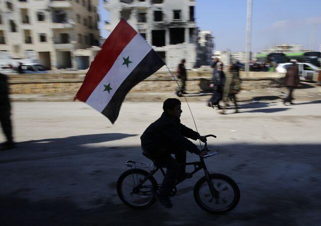 Un niño en bicicleta con la bandera de Siria (archivo)