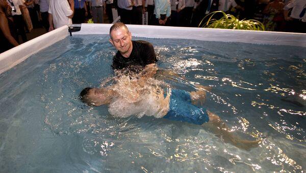 Una ceremonia del baptismo de los Testigos de Jehová - Sputnik Mundo