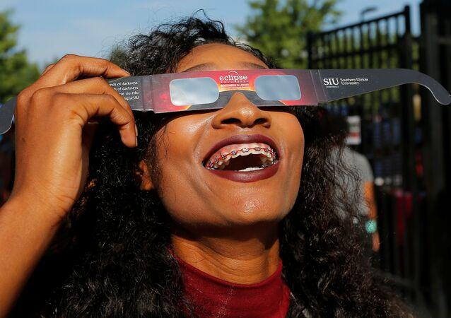 Una muchacha prueba gafas con filtro solar antes del eclipse del Sol del 21 de agosto de 2017