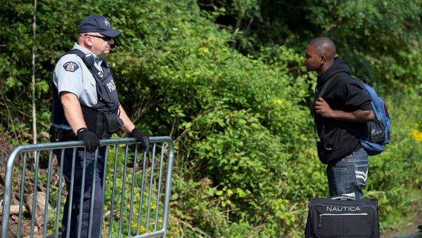 Un hombre haitiano espera cruzar la frontera entre EEUU y Canadá - Sputnik Mundo