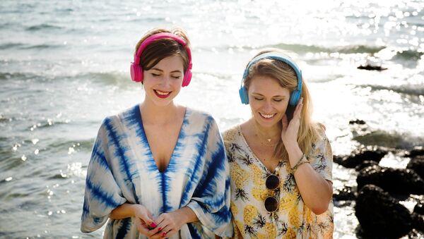 Unas chicas, escuchando música en la costa - Sputnik Mundo