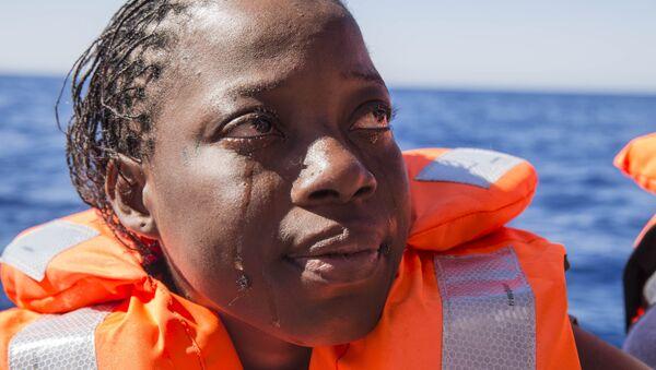 Una mujer de Costa de Marfil llora después de haber sido rescatada por los equipos de búsqueda y rescate de Médicos Sin Fronteras en el Mar Mediterráneo. - Sputnik Mundo