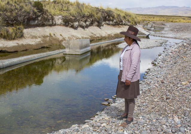 Marleny Surco mirando a su fuente de agua contaminada. Habitante de la comunidad de Espinar