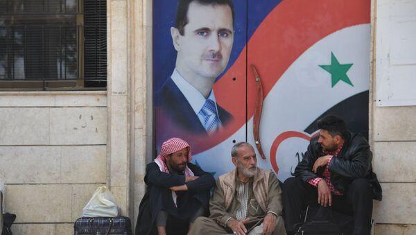 Los sirios junto al retrato de Bashar Asad, presidente de Siria (archivo) - Sputnik Mundo