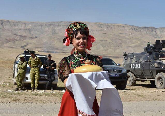 Una artista rusa recibe a los militares con el tradicional pan de bienvenida