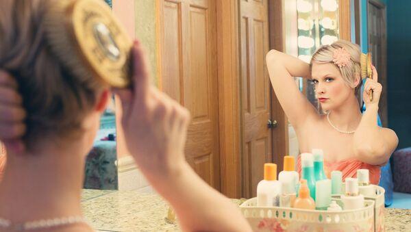 Una mujer mira en un espejo - Sputnik Mundo